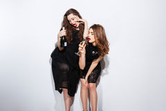 Two sexy women in night dress drinking champagne Stock Images