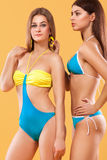 Two sexy women in swimwear posing on orange background. Perfect body. Bikini summer advertisement concept. Sexy yang girls standing on a solid color background Royalty Free Stock Images