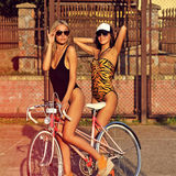 Two sexy women with vintage bike. Outdoor fashion portrait Stock Photo