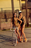 Two sexy women with vintage bike. Outdoor fashion portrait Stock Image