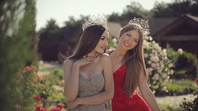 Two sexy young female in the long gowns and crowns. Two sexy young female in long gowns and crowns smiling and posing in the park with roses stock footage