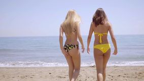 Two sexy young girls in bikinis. Crossing the sandy beach towards the sea  close up view from behind stock video