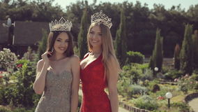 Two sexy young girls in evening gowns and crowns stock video