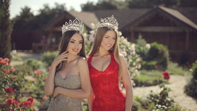 Two sexy young women posing in evening gowns and. Crowns in beautiful garden stock video