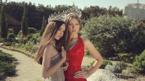 Two sexy young women posing in evening gowns and. Crowns in beautiful garden stock footage