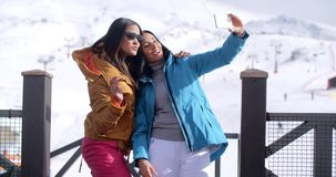 Two sexy young women posing for a selfie. As they stand together on a balcony on a chalet at a mountain ski resort with winter snow stock video footage