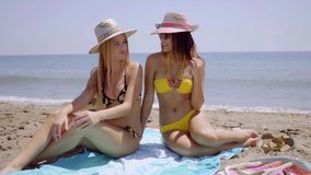 Two sexy young women sunbathing on a beach stock video