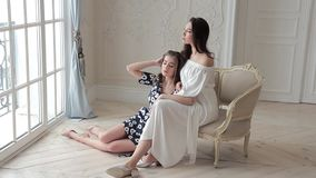 Two sexy young wonen posing for a catalog photo in romantic dresses stock footage