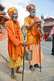 Two Shaiva sadhu walking alms in front of a temple Royalty Free Stock Images
