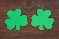 Two Shamrocks on Wood. Two green shamrocks side by side on aged andmeather beaten brown knotted wood stock images