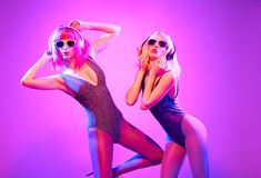 Two shapely DJ girl with Dyed Hair dance. Art neon royalty free stock image