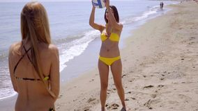 Two shapely women playing with a beach ball stock video footage