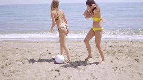 Two shapely young woman playing on a beach. Two shapely young woman wearing bikinis playing on a beach kicking a ball across the golden sand  full length with stock footage