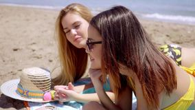 Two shapely young women in bikinis. Two shapely attractive young women in bikinis lying side by side on the beach sand on their towels sunbathing and chatting stock video footage