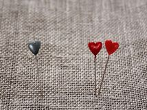 Two sharp pins in the form of red hearts near and one blue stuck Stock Photo