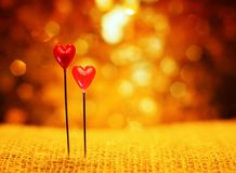 Two sharp pins in the form of red hearts stuck in the burlap on Royalty Free Stock Photos
