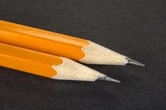 Two sharpened pencils on a black background royalty free stock image