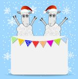 Two sheep and greeting-card with a garland Royalty Free Stock Photography