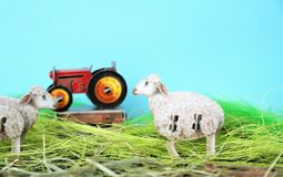 Two sheep, tractor and blue background stock image