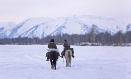 Two shepherd or cowboy riding a horse go away to the snowy mountains on Novemer 1, 2016 Altai, Russia Royalty Free Stock Photo