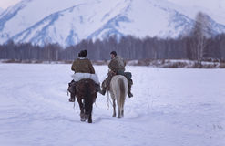 Two shepherd or cowboy riding a horse go away to the snowy mountains on Novemer 1, 2016 Altai, Russia Stock Photos
