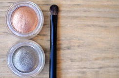 Two shimmer eyeshadow glass boxes and brush on wood table Royalty Free Stock Images