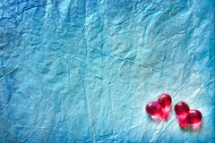 Two shining hearts over blue background. Two shining hearts over blue wrapping paper background Stock Image