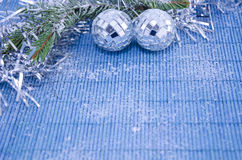 Two shiny disco balls on a fir branch covered with snow Stock Photos