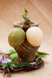 Two shiny easter eggs with ceramic vase and ornamental wicker Royalty Free Stock Images