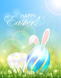 Two shiny Easter eggs and rabbit ears in the grass Stock Image