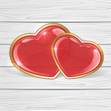 Two shiny hearts on wooden background Stock Photos
