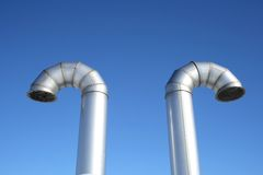 Two shiny metal ventilation pipes. Two shiny metallic ventilation pipes on a blue sky background royalty free stock images