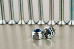 Two shiny nuts against some smooth metal bolts Royalty Free Stock Photo
