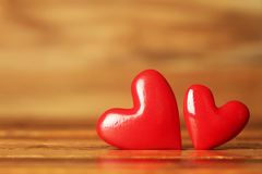 Shiny red hearts on wooden background. Two shiny red hearts on wooden background Royalty Free Stock Images
