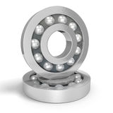 Two shiny steel ball bearings on a white background, one balanced on the other Royalty Free Stock Photos