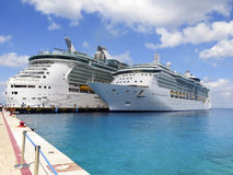 Two Ships. Two Cruise Ships tied together on one pier with blue water and sky Royalty Free Stock Image