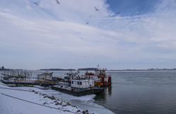 Two ships near a pontoon mooring on Danube river in a city from Romania on winter season Royalty Free Stock Photo