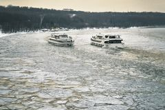 Two ships sailing along the Moscow-River covered with a broken ice towards each other. Two pleasure crafts sailing along the Moscow-River covered with a broken Stock Photo