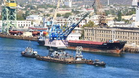 Two ships tow the crane on the sea gulf. Sevastopol. The towing vessel is towing a floating crane at seaport in Savastopol stock footage