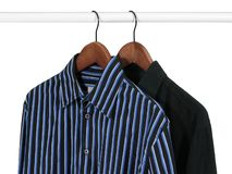 Two shirts on a rack. Black and blue shirts on hangers on a rack, on white background royalty free stock photo