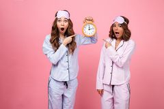 Two shocked confused screaming friends women holding alarm Royalty Free Stock Photo