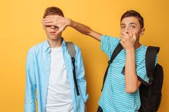 Two shocked teenagers close their eyes against a yellow background for fear. Two shocked teenagers close their eyes against stock images