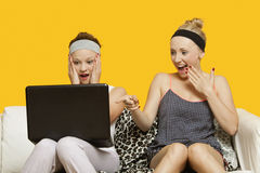 Two shocked young women using laptop sitting on sofa against yellow background Stock Image