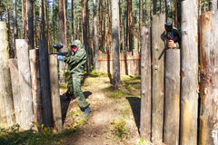 Two shooters with paintball guns defend wooden fortress. Outdoors Royalty Free Stock Image