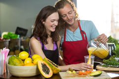 Two shop assistants pouring the juice into the glass. At health grocery shop Royalty Free Stock Image