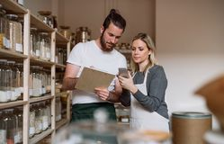 Two shop assistants standing at the counter in zero waste shop, checking stock. Two shop assistants standing at the counter in zero waste shop, checking and royalty free stock photo