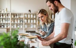 Two shop assistants standing at the counter in zero waste shop, checking stock. Two shop assistants standing at the counter in zero waste shop, checking and royalty free stock photos