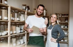 Two shop assistants standing in zero waste shop, checking stock. Two shop assistants standing in zero waste shop, checking and ordering stock royalty free stock photos