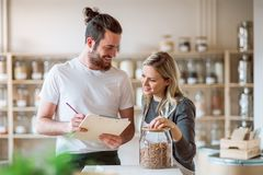 Two shop assistants standing in zero waste shop, checking stock. Two shop assistants standing in zero waste shop, checking and ordering stock stock images
