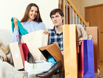 Two shopaholic together with clothes and bags Stock Photos
